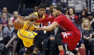 Indiana Pacers forward Paul George, left, works to retain possession as Washington Wizards guard Garrett Temple reaches for the ball during the second half of an NBA basketball game Saturday, March 5, 2016, in Washington. The Pacers won 100-99. (AP Photo/Alex Brandon)
