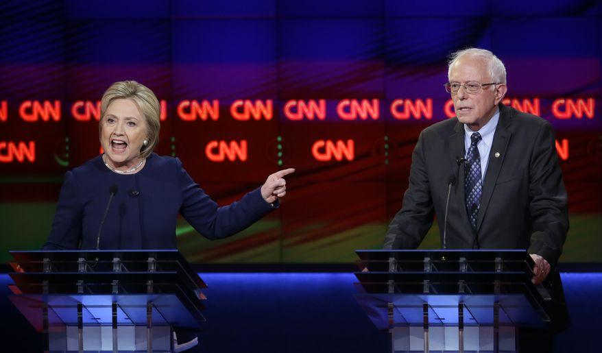 Hillary Clinton argues a point as Sen. Bernard Sanders listens during the Democratic debate Sunday night in Flint, Mich. (Associated Press) **FILE**