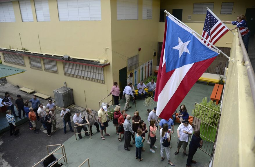 Puerto Rico's residents line up to vote during the U.S. territory's Republican primary at the Santurce County in San Juan, Puerto Rico, in this Sunday, March 6, 2016, file photo. Puerto Rico residents cannot participate in general presidential elections but can do so in primaries. Puerto Rico sends 20 delegates to the Republican convention. (AP Photo/Carlos Giusti)
