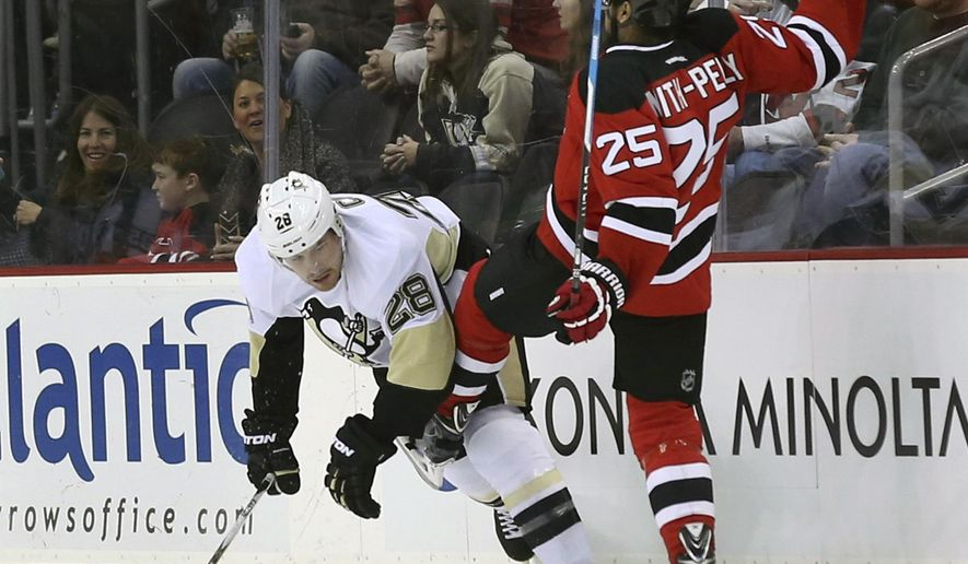 Pittsburgh Penguins defenseman Ion Cole (28) collides with New Jersey Devils right wing Devante Smith- Pelly (25) during the first period of an NHL hockey game Sunday, March 6, 2016, in Newark, N.J. (AP Photo/Mel Evans)