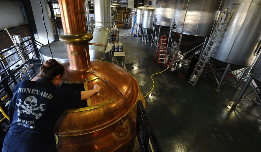 ADVANCE FOR WEEKEND EDITIONS - In this Feb. 24, 2016 photo, Dana Robles works on cleaning a tank during her shift at Boneyard Brewery in Bend, Ore. Northeast Bend is becoming a brewery district. The Bulletin reports Seven beer makers operate in the area. (Ryan Brennecke/The Bulletin via AP) MANDATORY CREDIT