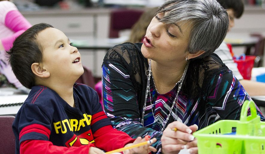 ADVANCE FOR RELEASE SATURDAY, MARCH 5, 2016, AT 12:01 A.M. MST. AND THEREAFTER - In this Feb. 16, 2016, photograph, kindergartner Michael Lowry Clare, left, works with dual-language teacher Yesenia Perez, to sound out words in Spanish as the rest of the class writes sentences in their journals at Cottonwood Plains Elementary School in Loveland, Colo. Test scores are improving among kindergartners at a Loveland school district who are learning in both English and Spanish. (Michael Bettis/Loveland Daily Reporter-Herald via AP) NO SALES; MANDATORY CREDIT