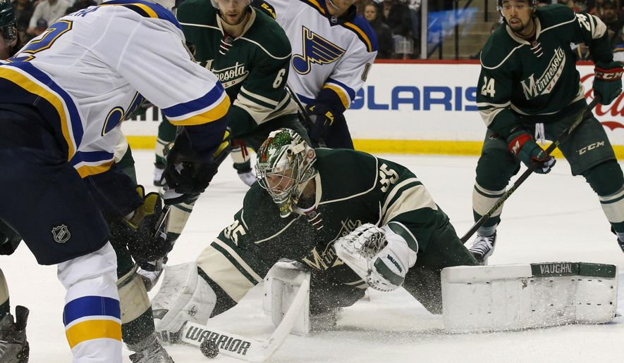 Minnesota Wild goalie Darcy Kuemper (35) swats away a shot by St. Louis Blues center Jori Lehtera, left, of Finland, during the second period of an NHL hockey game in St. Paul, Minn., Sunday, March 6, 2016. (AP Photo/Ann Heisenfelt)