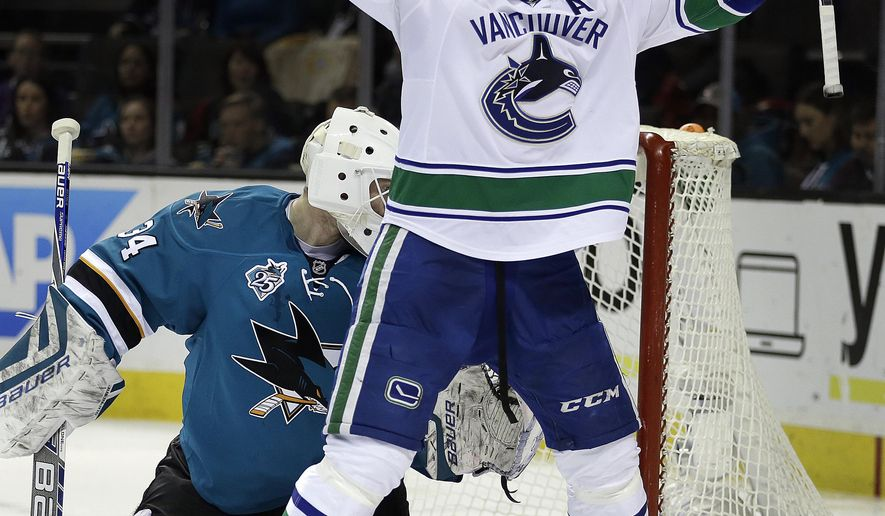 Vancouver Canucks' Daniel Sedin, right, celebrates after scoring a goal against San Jose Sharks goalie James Reimer (34) during the second period of an NHL hockey game Saturday, March 5, 2016, in San Jose, Calif. (AP Photo/Ben Margot)