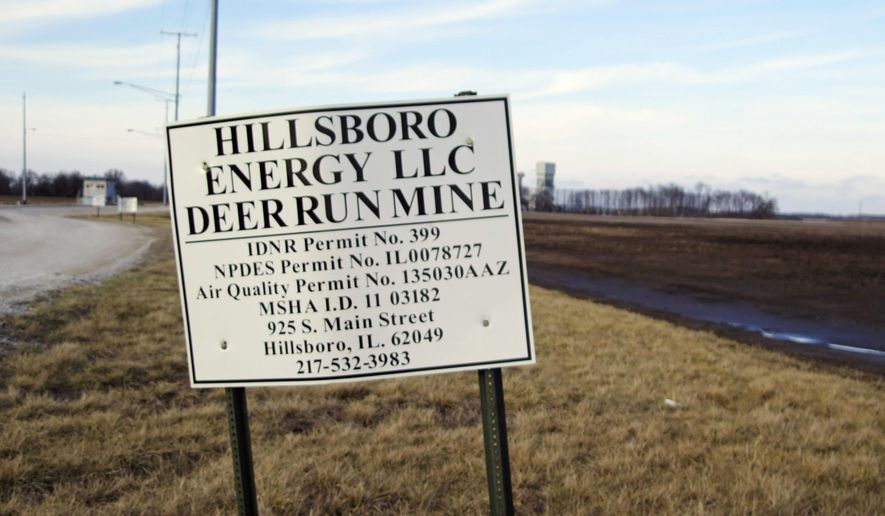 FILE - This Feb. 5, 2016, file photo shows a sign leading to the Deer Run coal mine, background, where a smoldering underground fire led owner Hillsboro Energy LLC, a subsidiary of Foresight Energy, to indefinitely shut down the southern Illinois facility near Hillsboro, Ill. As the mine owner seeks an expansion on a site unaffected by the fire, the state Attorney General's Office is considering legal action against the Illinois Department of Natural Resources for what prosecutors call a failure to follow the terms of a court-brokered plan to toughen oversight of the mine permit process. (AP Photo/Alan Scher Zagier, File)