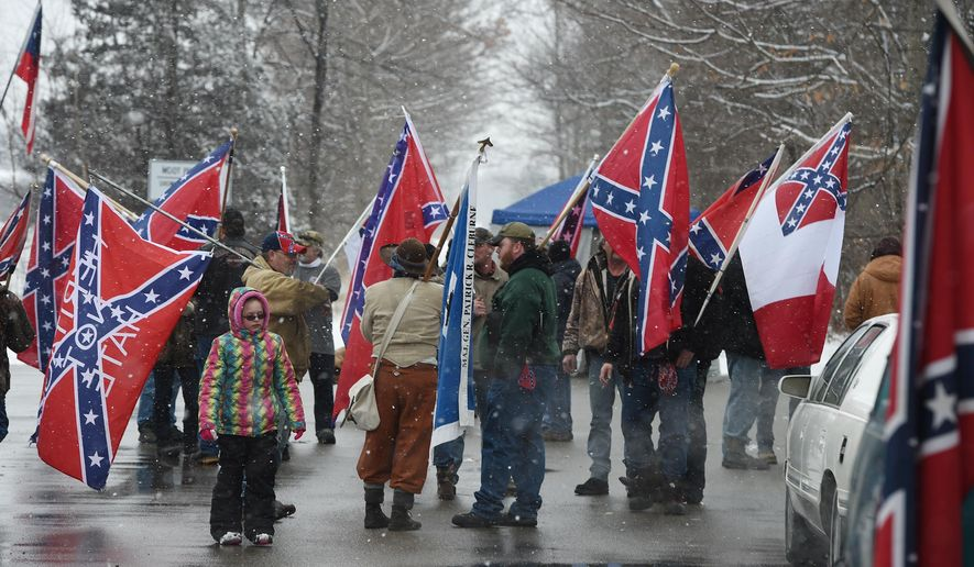 People hold Confederate flags and talk during a Confederate flag rally at the park and ride area on U.S. 127 near Jefferson Road on Saturday afternoon, March 5, 2016, in Jackson, Mich. About 30 people from across the state carried various versions of the flag in a carpool lot in Columbia Township, southwest of Detroit. (J. Scott Park/Jackson Citizen Patriot via AP)