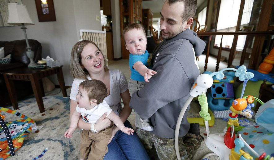 FOR RELEASE SUNDAY, MARCH 6, 2016, AT 12:01 A.M. CST.- Nicole and Jessie James of Asbury, Iowa with their 8-month-old twins Elliot (left) and Jacob Feb. 26, 2016.  (Nicole) James is a 2016 Caregiver Fellow with the Elizabeth Dole Foundation for her work in taking care of her Marine Corps veteran husband. (Dave Kettering/Telegraph Herald via AP)