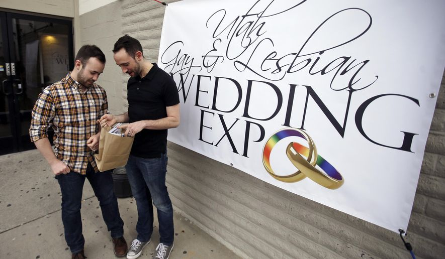 Engaged couple Will Bladh, left, and Jason Langlois look at their gift bag at a gay and lesbian wedding expo aimed at connecting same-sex couples with businesses who won't refuse to work on gay weddings Sunday, March 6, 2016, in Salt Lake City. That's a common occurrence in a state where florists, bakers and photographers have a legal right to refuse to serve a gay couple. (AP Photo/Rick Bowmer)