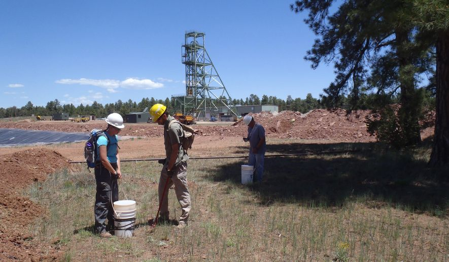 In this June 7, 2013, photo provided by the U.S. Geological Survey, Scientists, from left, Christine Dowling, Adam Benthem, and David Naftz collect soil samples on the Canyon Mine property in Arizona. The mine's headframe and mine workshop are visible in the background. Government scientists are studying the soil in the Grand Canyon region to determine the effect of uranium mining on the environment. (Katie Walton-Day/U.S. Geological Survey via AP) MANDATORY CREDIT