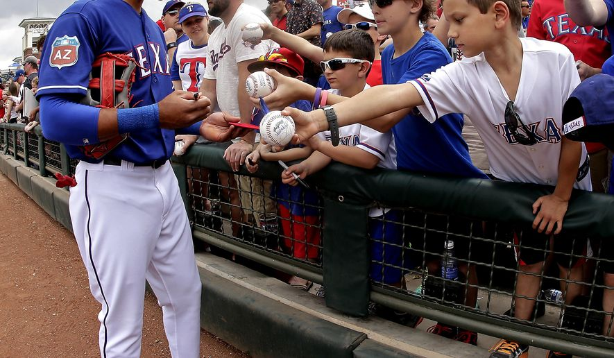 Texas Rangers' Ian Desmond signs autographs before a spring training baseball game against the Seattle Mariners Sunday, March 6, 2016, in Surprise, Ariz. (AP Photo/Charlie Riedel)