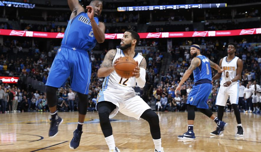 Dallas Mavericks guard Raymond Felton, left, fouls Denver Nuggets guard D.J. Augustin late in overtime of an NBA basketball game Sunday, March 6, 2016, in Denver. The Nuggets won 116-114 in overtime behind the two foul shots made by Augustin. (AP Photo/David Zalubowski)