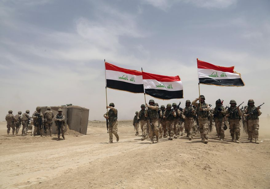 U.S. soldiers (left) participate in a training mission with Iraqi army soldiers outside Baghdad on May 27, 2015. (Associated Press) **FILE**