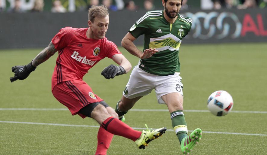 Columbus Crew goalkeeper Steve Clark, left, clears the ball as Portland Timbers midfielder Diego Valeri, right, closes in during the first half of an MLS soccer match in Portland, Ore., Sunday, March 6, 2016. (AP Photo/Steve Dipaola)
