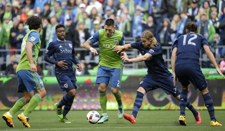 Seattle Sounders forward Clint Dempsey, center, kicks the ball as Sporting Kansas City defender Chance Myers, second from right, moves in to defend in the first half of an MLS soccer match, Sunday, March 6, 2016, in Seattle. (AP Photo/Ted S. Warren)