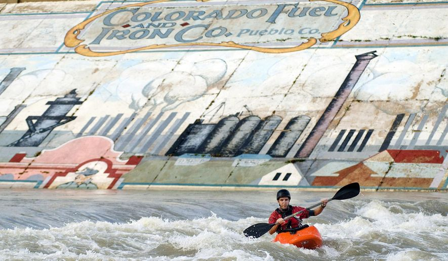 ADVANCE FOR SATURDAY, MARCH 5 AND THEREAFTER - In a July 2006 photo, kayaker Jeff Mara paddles in the shadow of a CF&I mural in the Pueblo Whitewater Park in Pueblo, Colo. The levee, including this iconic mural that has been replicated in a local museum, is being torn down and rebuilt. (Bryan Kelsen/The Pueblo Chieftain via AP) Kayaker Jeff Mara paddles in the shadow of a CF&I mural in the Pueblo Whitewater Park iin Pueblo, Colo. (Bryan Kelsen/The Pueblo Chieftain via )