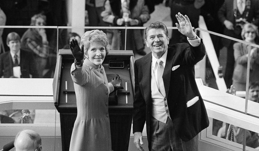 President Ronald Reagan and first lady Nancy Reagan wave to onlookers at the Capitol building as they stand at the podium in Washington following the swearing in ceremony. (AP Photo/File)