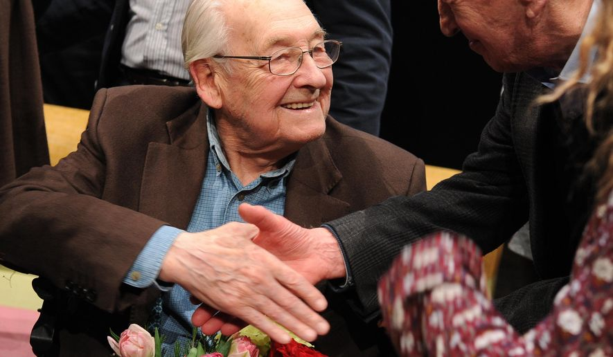 In this Thursday, March 3, 2016 photo Academy Award winning Polish film director Andrzej Wajda shakes hands with a spectator during the opening of a review of some of his movies held on the occasion of his birthday, in Warsaw, Poland. Wajda, who turns 90 on March 6, 2016, is currently working on his latest film. (AP Photo/Alik Keplicz)