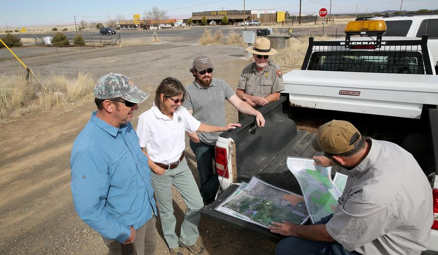 In this Tuesday, March 1, 2016, photo, from left to right, Roger Joos, wildlife biologist with the Kaibab National Forest; Cary Thompson, wildlife biologist with the Coconino National Forest; Rob Nelson, district environmental coordinator with the Arizona Department of Transportation; Paul Whitefield, natural resources specialist for the Flagstaff Area National Monuments; and Jeff Gagnon, statewide research biologist for the Arizona Game and Fish Department, gather around maps showing pronghorn migration, in Flagstaff, Ariz. Wildlife officials are modifying and moving fences and better tracking the movements of pronghorn antelope. (Jake Bacon/Arizona Daily Sun via AP) MANDATORY CREDIT