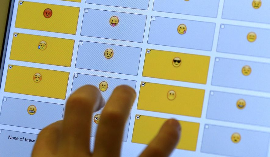 In this Feb. 15, 2016 photo, a student demonstrates how emojis are used during a research session on the Kansas State University campus in Olathe, Kan. The Sensory and Consumer Research Center at Kansas State University-Olathe is developing a scientific methodology to measure children's responses to food using face emojis. (AP Photo/Orlin Wagner)