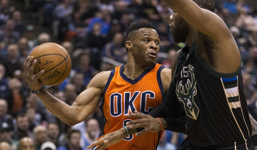 Milwaukee Bucks' Greg Monroe tries to defend as Oklahoma City Thunder's Russell Westbrook passes the ball during the first half of an NBA basketball game Sunday, March 6, 2016, in Milwaukee. (AP Photo/Tom Lynn)