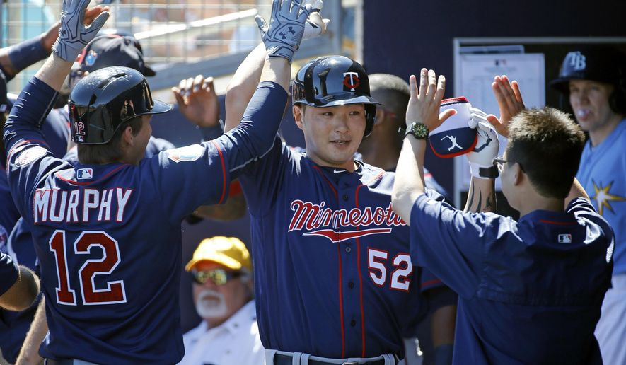 Minnesota Twins' Byung Ho Park, center, of South Korea, high-fives teammates in the dugout after hitting a grand slam in the first inning of a spring training baseball game against the Tampa Bay Rays in Port Charlotte, Fla., Sunday, March 6, 2016. (AP Photo/Patrick Semansky)