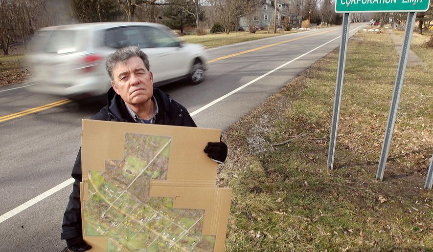 In a Feb.18, 2016 photo, Washington Township Trustee Dennis Cooper with a map he had made that uses yellow dots to designate FEMA owned property in the village of Neville, Ohio. Cooper estimated 40 percent of the village property; is owned by FEMA because it is in a flood plain and cannot be used for building Residents will vote next month on whether or not to dissolve the village.  (Patrick Reddy/The Enquirer via AP) NO SALES