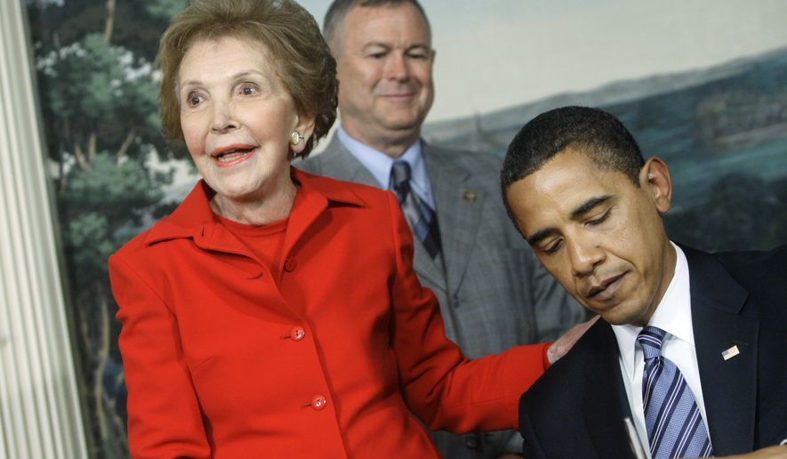 Former first lady Nancy Reagan smiles as President Barack Obama signs the Ronald Reagan Centennial Commission Act, Tuesday, June 2, 2009, during a ceremony in the Diplomatic Reception Room at the White House in Washington. Rep. Dana Rohrabacher. R-Calif. is at center.  (AP Photo/Haraz N. Ghanbari)