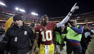 Washington Redskins quarterback Robert Griffin III (10) celebrates as he comes off the field after an NFL football game against the Dallas Cowboys on Sunday, Dec. 30, 2012, in Landover, Md. The Redskins won 28-18, securing a playoff berth. (AP Photo/Evan Vucci)