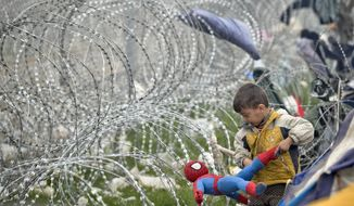 A boy untangles a Spiderman doll caught in the razor wire around the fence between Greece and Macedonia at the northern Greek border station of Idomeni, Monday, March 7, 2016. (AP Photo/Vadim Ghirda)