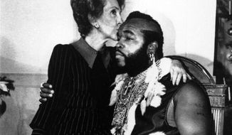 First lady Nancy Reagan sits on the knee of television personality Mr. T, dressed as Santa Claus, as he joined her for a preview of the White House Christmas decor on Dec. 12, 1983 in Washington, D.C. (Associated Press)
