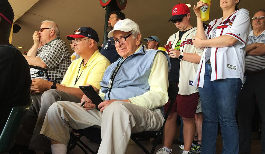Tommy Giordano, special assistant to the general manager of the Atlanta Braves, scouts an exhibition spring training baseball game between the Braves and the Pittsburgh Pirates, Saturday, March 5, 2016, in Kissimmee, Fla. Giordano sits in a folding chair behind home plate at Champion Stadium, a stopwatch in his right hand, a lineup card in his lap, his eyes darting this way and that, always searching for the next Joe DiMaggio. At age 90, Giordano enters his 69th year in professional baseball with no plans to retire and his passion for the game as strong as ever. (AP Photo/Paul Newberry)
