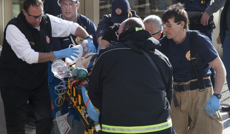 First responders work to revive a woman who shot herself in the chest in front of the courthouse and Alaska's Capitol on Monday, March 7, 2016, in Juneau, Alaska.  The shooting occurred in front of the building, which is directly across the street from the state Capitol.  Juneau police said she could not be resuscitated and was declared dead at the hospital. (AP Photo/Rashah McChesney)