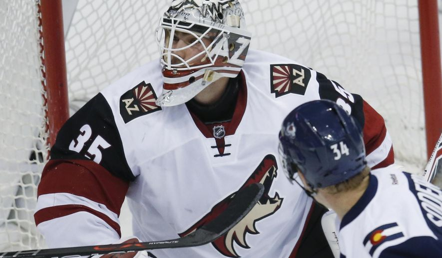 Arizona Coyotes goalie Louis Domingue has the puck filly over his head after stopping a shot off the stick of Colorado Avalanche center Carl Soderberg, of Sweden, in the first period of an NHL hockey game Monday, March 7, 2016, in downtown Denver. (AP Photo/David Zalubowski)