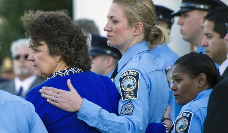 Sharon Guindon, left, mother of Prince William County, Va. Police Officer Ashley Guindon is comforted by a Prince William County Police Officer as they depart the Hylton Memorial Chapel following Officer Guindon's funeral, Tuesday, March 1, 2016, in Woodbrige, Va.  (AP Photo/Cliff Owen)