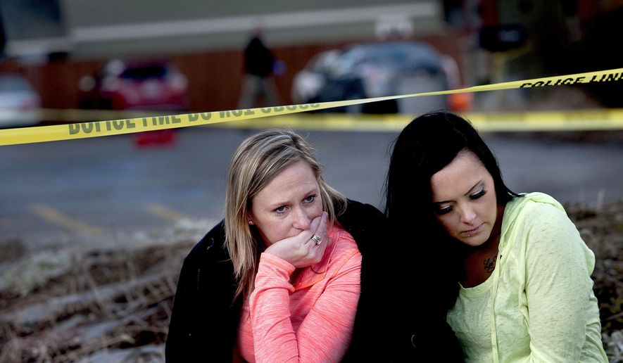 In this Sunday, March 6, 2016, photo, Amanda Padula, left, and Deborah Young sit outside Altar Church in Coeur d'Alene, Idaho, where pastor Tim Remington was shot multiple times as he was leaving services earlier in the day. The two women said they benefited from Remington's Good Samaritan Rehabilitation program. (Kathy Plonka/The Spokesman-Review via AP)