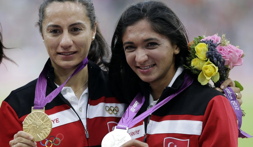 FILE - In this Aug. 11, 2012 file photo  Turkey's silver medal winner Gamze Bulut, is flanked byTurkey's gold medal winner Asli Cakir Alptekin, left, as they pose with their medals for the women's 1500-meter during the athletics in the Olympic Stadium at the 2012 Summer Olympics, London. Olympic 1,500-meter silver medalist Gamze Bulut is under investigation by the International Association of Athletics Federations for a possible doping violation it was confirmed Monday March 7, 2016.   (AP Photo/Matt Slocum, file)