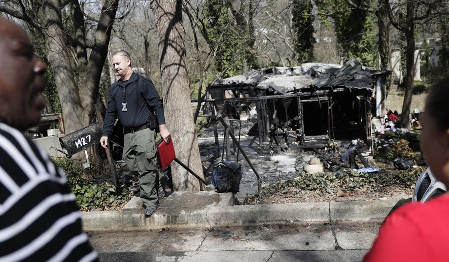 An investigator walks in front of the scene of a house fire where an Atlanta fire spokesman says six people were killed Monday, March 7, 2016, in Atlanta. Atlanta Fire Rescue spokesman Cortez Stafford said that four men and two women perished in the Monday morning blaze on the city's northwest side. He said the cause of the fire had not yet been determined.(AP Photo/David Goldman)