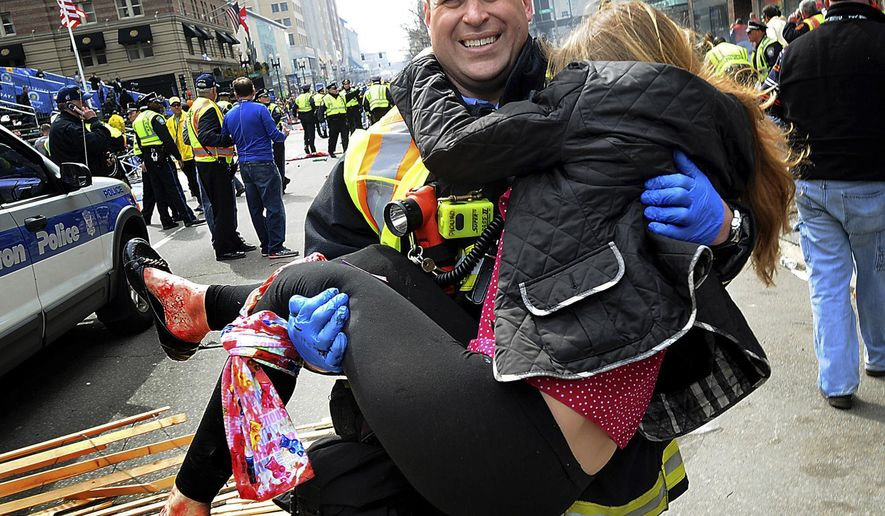 FILE - In this April 15, 2013 file photo, Boston Firefighter James Plourde carries Victoria McGrath from the scene after a bombing near the Boston Marathon finish line. A Northeastern University spokesman said Monday, March 7, 2016, that McGrath, originally from Westport, Conn., and another student were killed in a car accident in Dubai over the weekend while on a personal trip. (AP Photo/MetroWest Daily News, Ken McGagh, File) MANDATORY CREDIT: METROWEST DAILY NEWS, KEN MCGAGH
