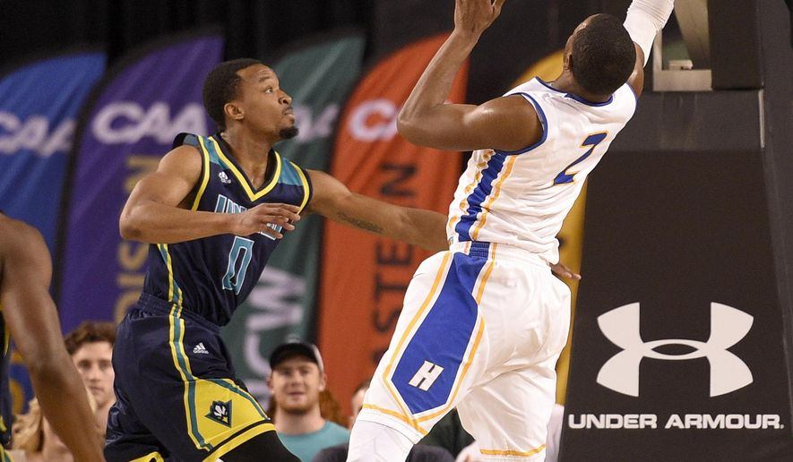 Hofstra guard Ameen Tanksley (2) goes to th basket against UNC Wilmington guard Craig Ponder (0) during the first half of an NCAA college basketball game in the Colonial Athletic Association championship, Monday, March 7, 2016, in Baltimore. (AP Photo/Nick Wass)