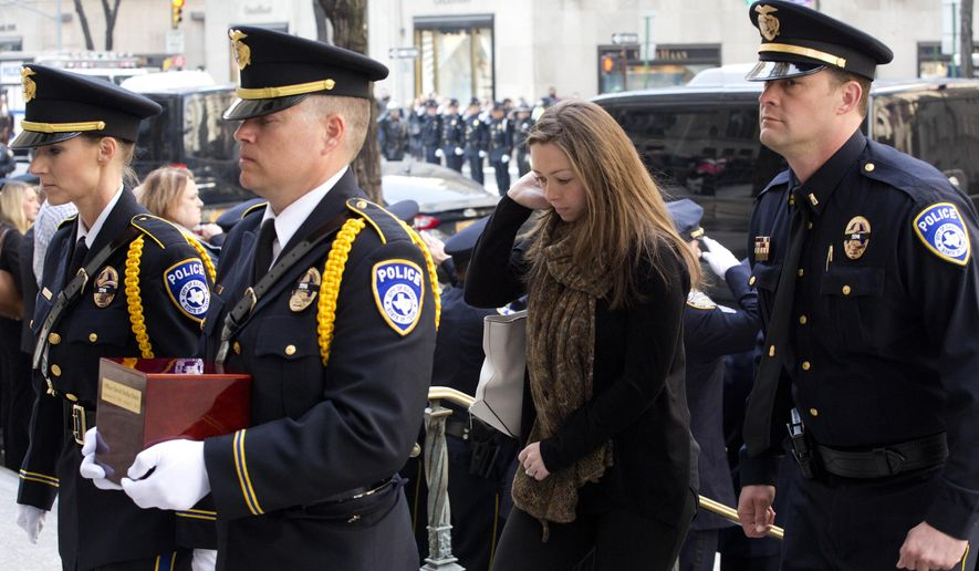Marta Danylyk, second from right, arrives for the funeral mass for her fiancee, Euless, Texas, Police Officer David Hofer, Monday, March 7, 2016, at St. Patrick's Cathedral in New York. Hofer was killed Tuesday, March 1 while responding to reports of shots fired in a park. Hofer was a 2008 graduate of New York University who served in the NYPD for five years before joining the Euless Police Department in 2014. (AP Photo/Mark Lennihan)