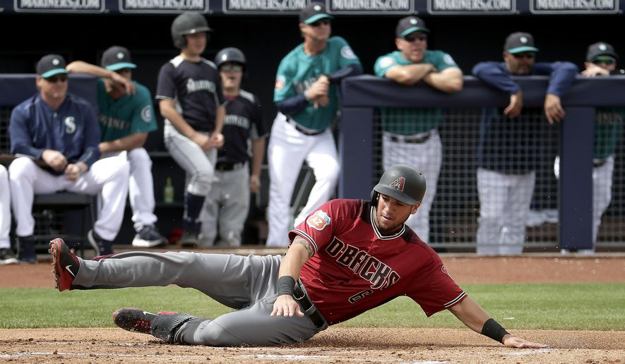 Arizona Diamondbacks' David Peralta slides home to score on a two-run double by Welington Castillo during the first inning of a spring training baseball game against the Seattle Mariners Monday, March 7, 2016, in Peoria, Ariz. (AP Photo/Charlie Riedel)