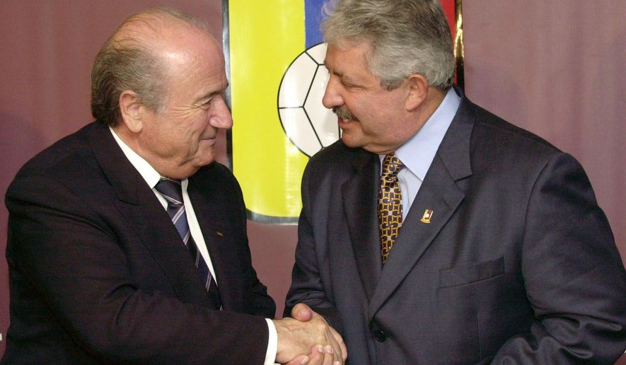 FILE - In this Nov. 8, 2004 file photo Sepp Blatter, President of the FIFA, left, shakes hands with the President of the Venezuelan Soccer Federation, Rafael Esquivel, in Caracas, Venezuela. Switzerland's justice ministry said on Monday, March 7, 2016, that the former Venezuela soccer federation president, Rafael Esquivel, has been extradited to face bribery charges in the United States in the widening FIFA case. (AP Photo/Leslie Mazoch, File)
