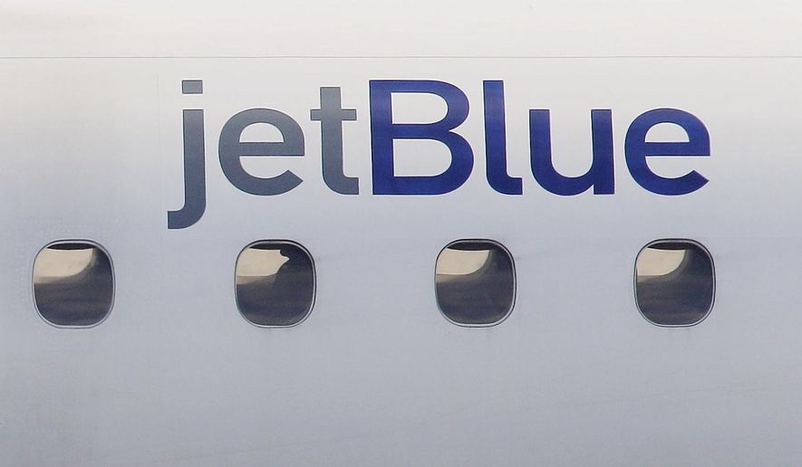 In this Jan. 20, 2011, file photo, a JetBlue logo is displayed on the side of a jet as it taxis at Boston's Logan International Airport.   (AP Photo/Stephan Savoia, File) **FILE**