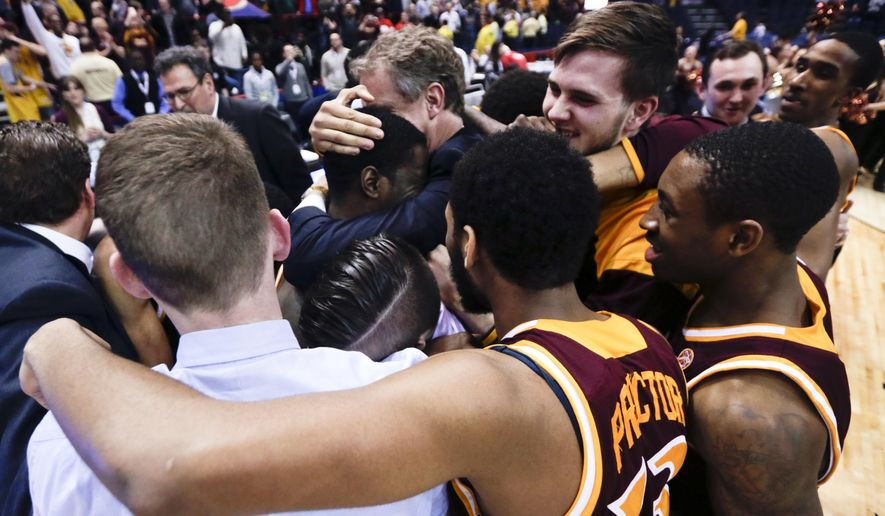 Iona players and coaches celebrate their 79-76 win over Monmouth in an NCAA men's college basketball game in the championship of the Metro Atlantic Athletic Conference tournament on Monday, March 7, 2016, in Albany, N.Y. (AP Photo/Mike Groll)