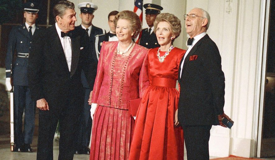 In this Nov. 16, 1988 photo, President Ronald Reagan, left, and first lady Nancy Reagan, second right, appear with British Prime Minister Margaret Thatcher, second left, and her husband, Dennis at a state dinner at the White House in Washington. Nancy Reagan died Sunday, March 6, 2016, at the age of 94. (AP Photo/Charles Tasnadi, File)