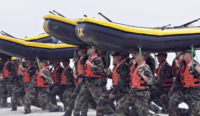 In this May 14, 2009, file photo, Navy SEAL trainees carry inflatable boats at the Naval Amphibious Base Coronado in Coronado, Calif. (AP Photo/Denis Poroy, File)