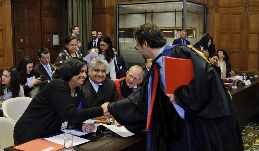 Members of the Indian delegation to the International Court of Justice, Neeru Chadha, left, and Harish Salve, center,  greet a member of the Marshall Islands' legal team ahead of a preliminary hearing on nuclear disarmament at the International Court of Justice in The Hague, Netherlands, Monday, March 7, 2016. The Marshall Islands, home to the Bikini Atoll nuclear testing site, is urging nuclear powers India, Pakistan and Britain to resume disarmament negotiations. (AP Photo/Mike Corder)