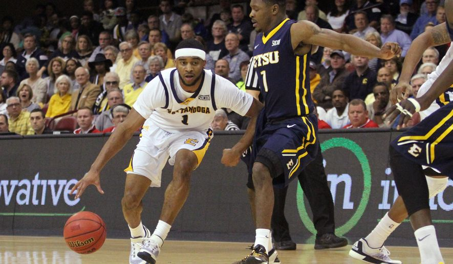 Chattanooga's Greg Pryor (1) pushes his way towards the basket against East Tennessee State's Desonta Bradford (11) during the first half of the championship game of the NCAA men's Southern Conference basketball tournament in Asheville, N.C., Monday, March 7, 2016. (AP Photo/Ben Earp)