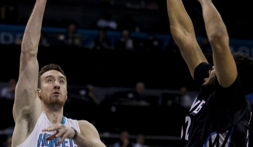 Charlotte Hornets forward Frank Kaminsky, left, shoots against Minnesota Timberwolves center Karl-Anthony Towns in the first half of an NBA basketball game in Charlotte, N.C., Monday, March 7, 2016. (AP Photo/Nell Redmond)