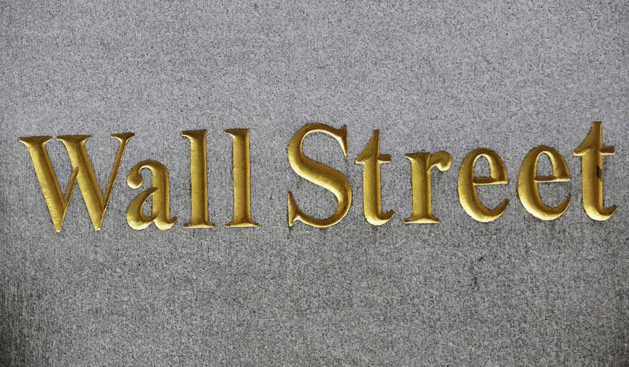 FILE - This Monday, July 6, 2015, file photo, shows a sign for Wall Street carved into the side of a building, in New York. Average Wall Street bonuses were down 9 percent in 2015 to $146,200 as industry profits declined, New York's comptroller reported Monday, March 7, 2016. (AP Photo/Mark Lennihan, File)